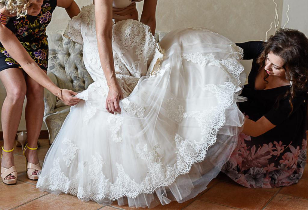 Oxana indossa l'abito, aiutata dalle sue damigelle